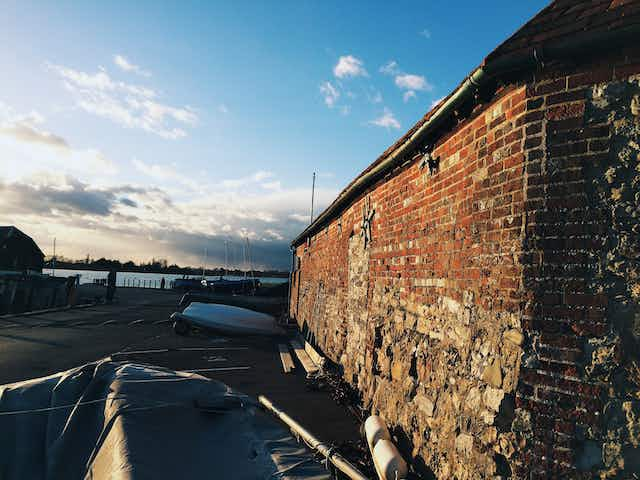 An aging brick boathouse and a cloudy sky near sunset